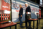 Iowa Gov. Kim Reynolds, left, walks off the stage with Roger Penske after a news conference at Hy-Vee Corp. headquarters, Thursday, Aug. 19, 2021, in West Des Moines, Iowa. IndyCar will return next season to Iowa Speedway, a short oval track beloved by fans and drivers that had fallen off the schedule after 14 years. The track located in Newton will host a doubleheader next July in a deal brokered between IndyCar Series owner Roger Penske, team owner Bobby Rahal and grocery chain Hy-Vee. (AP Photo/Charlie Neibergall)
