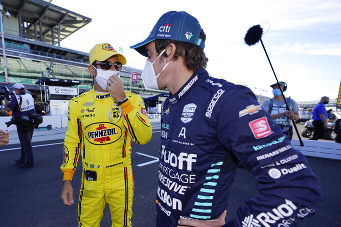 Helio Castroneves, of Brazil, left, and Fernando Alonso, of Spain, talks before the final practice session for the Indianapolis 500 auto race at Indianapolis Motor Speedway, Friday, Aug. 21, 2020, in Indianapolis. (AP Photo/Darron Cummings)