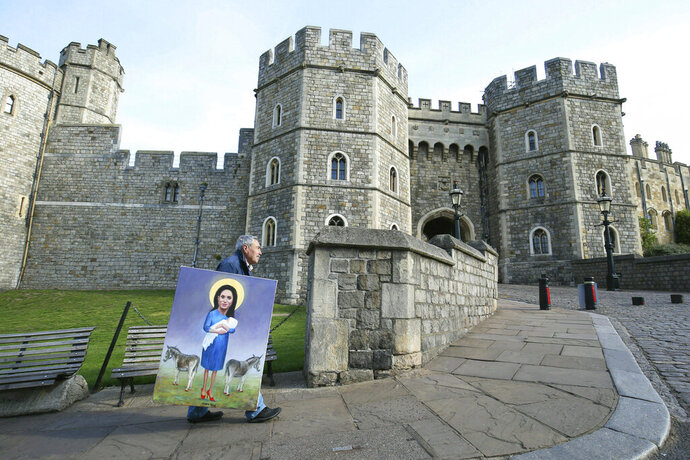 Political artist Kaya Mar walks with his latest work past Windsor Castle in Windsor, England, following the announcement of the birth of a baby boy to Britain's Prince Harry and Meghan, the Duchess of Sussex, Tuesday, May 7, 2019. The as-yet-unnamed baby arrived less than a year after Prince Harry wed Meghan Markle in a spectacular televised event on the grounds of Windsor Castle that was watched the world over. (Jonathan Brady/PA via AP)