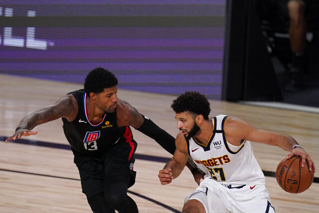 Denver Nuggets' Jamal Murray (27) drives past Los Angeles Clippers' Paul George (13) during the second half of an NBA conference semifinal playoff basketball game Saturday, Sept. 5, 2020, in Lake Buena Vista, Fla. (AP Photo/Mark J. Terrill)