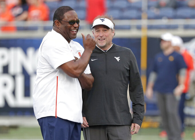Syracuse head coach Dino Babers, left, and West Virginia head coach Dana Holgorsen greet each other at midfield before the start of the Camping World Bowl NCAA college football game Friday, Dec. 28, 2018, in Orlando, Fla. (AP Photo/John Raoux)