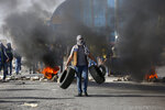 Palestinian demonstrators burn tires as they clash with Israeli troops during the protest against the U.S. announcement that it no longer believes Israeli settlements violate international law., at checkpoint Beit El near the West Bank city of Ramallah, Tuesday, Nov. 26, 2019, (AP Photo/Majdi Mohammed)