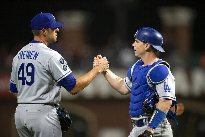 Los Angeles Dodgers pitcher Blake Treinen (49) and catcher Will Smith celebrate the team's 2-1 victory over the San Francisco Giants in a baseball game Friday, May 21, 2021, in San Francisco. (AP Photo/D. Ross Cameron)