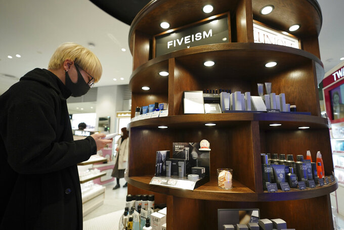 Customer Kenta Yamazaki, a 24-year-old hairdresser, looks at beauty products at @cosme TOKYO, a store selling a selection of cosmetics and makeup products including men's cosmetic, in Tokyo's Harajuku district Tuesday, Feb. 9, 2021. The coronavirus pandemic has been pushing businesses to the edge in Japan, but some in the men's beauty industry have seen an unexpected expansion in their customer base. Japanese businessmen in their 40s, 50s and 60s who had little interest in cosmetics before the pandemic are now buying makeup. (AP Photo/Eugene Hoshiko)