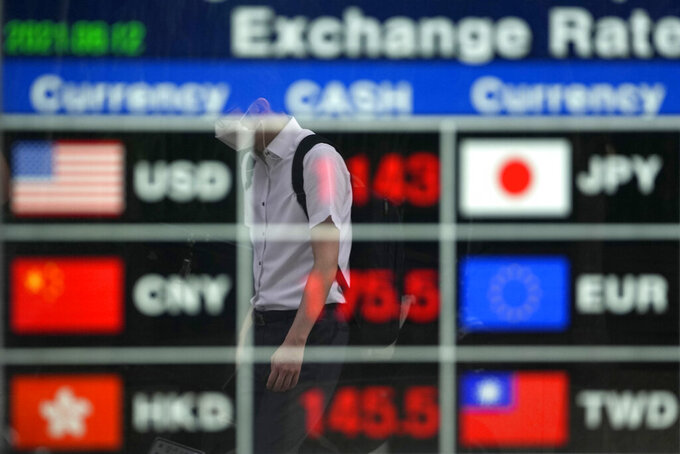 A man wearing a face mask is reflected on an electronic foreign currency exchange rates in downtown Seoul, South Korea, Thursday, Aug. 12, 2021. Asian shares were mixed Thursday as caution set in among investors following another wobbly day of trading on Wall Street.  (AP Photo/Lee Jin-man)