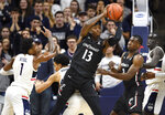 Cincinnati's Tre Scott (13) pulls down a rebound over Connecticut's James Bouknight, bottom, in the first half of an NCAA college basketball game, Sunday, Feb. 9, 2020, in Storrs, Conn. (AP Photo/Jessica Hill)