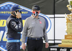 Martin Truex Jr. talks on a cell phone as team owner Joe Gibbs stands nearby after Truex won the NASCAR Cup Series auto race at Darlington Raceway, Sunday, May 9, 2021, in Darlington, S.C. (AP Photo/Terry Renna)