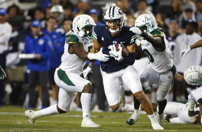 BYU wide receiver Neil Pau'u (2) runs for a fist down as South Florida linebacker Antonio Grier (5) and South Florida defensive back Daquan Evans (0) pursue in the second half of an NCAA college football game Saturday, Sept. 25, 2021, in Provo, Utah. (AP Photo/George Frey)