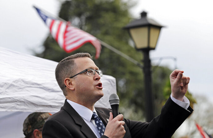FILE - In this Jan. 18, 2019, file photo, state Rep. Matt Shea, R-Spokane Valley, speaks at a gun-rights rally at the Capitol in Olympia, Wash. The mayor and police chief of Spokane, Wash., are the latest to demand that the conservative state legislator resign from office after leaked emails revealed he sought to conduct surveillance on local progressive leaders. Mayor David Condon and Police Chief Craig Meidl on Tuesday, Aug. 20, 2019 denounced Shea, who wants to create a 51st state based on Christian principles. (AP Photo/Ted S. Warren, File)