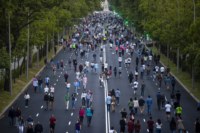 People walk along Paseo de la Castellana after the lockdown measures imposed by the government due to coronavirus in Madrid, Spain, Saturday, May 9, 2020. Spain has become the first western Europe to accumulate more than 1 million confirmed infections as the country of 47 million inhabitants struggles to contain a resurgence of the coronavirus. (AP Photo/Manu Fernandez)