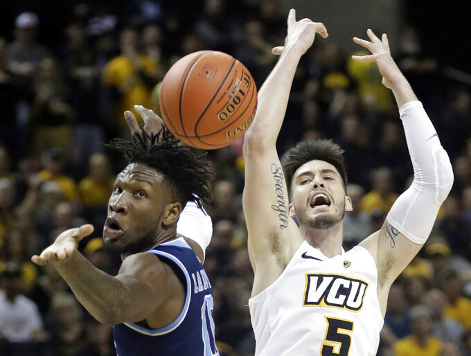 Rhode Island's Cyril Langevine (10), left, knocks the ball away from VCU's Sean Mobley (5) during the first half of an NCAA college basketball game in the Atlantic 10 men's tournament Friday, March 15, 2019, in New York. (AP Photo/Frank Franklin II)
