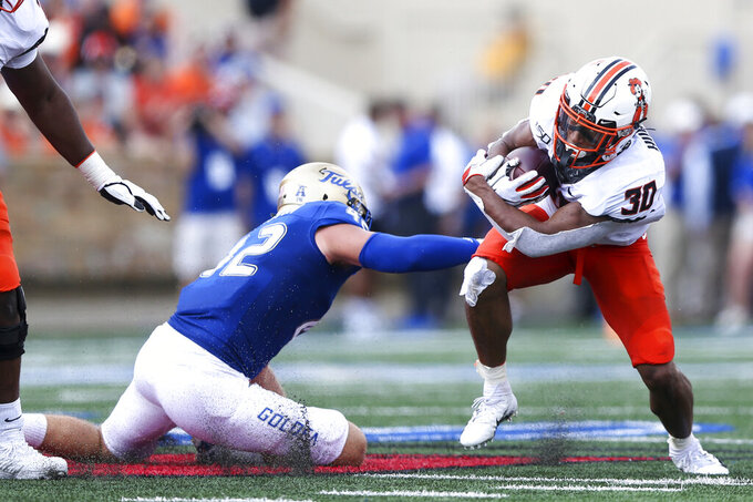 Oklahoma State running back Chuba Hubbard (30) attempts to avoid a tackle by Tulsa linebacker Cooper Edmiston (42) during an NCAA college football game Saturday, Sept. 14, 2019, in Tulsa, Okla. (Ian Maule/Tulsa World via AP)