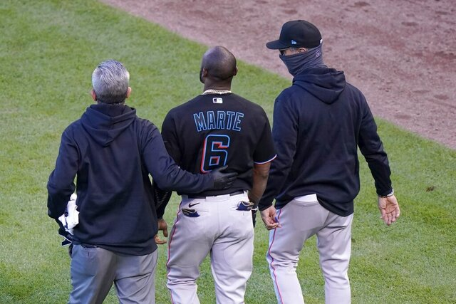 A member of the Miami Marlins staff and manager Don Mattingly, right, lead Starling Marte (6) away after Marte was hit by a pitch in the ninth inning of Game 1 of a National League wild-card baseball series against the Chicago Cubs in Chicago, Wednesday, Sept. 30, 2020. Marte left the game with an unknown injury. (AP Photo/Nam Y. Huh)