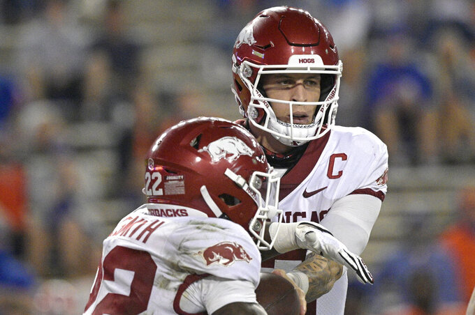 Arkansas quarterback Feleipe Franks hands the ball off to running back Trelon Smith (22), who carried for an 83-yard touchdown during the first half of the team's NCAA college football game against Florida, Saturday, Nov. 14, 2020, in Gainesville, Fla. (AP Photo/Phelan M. Ebenhack)