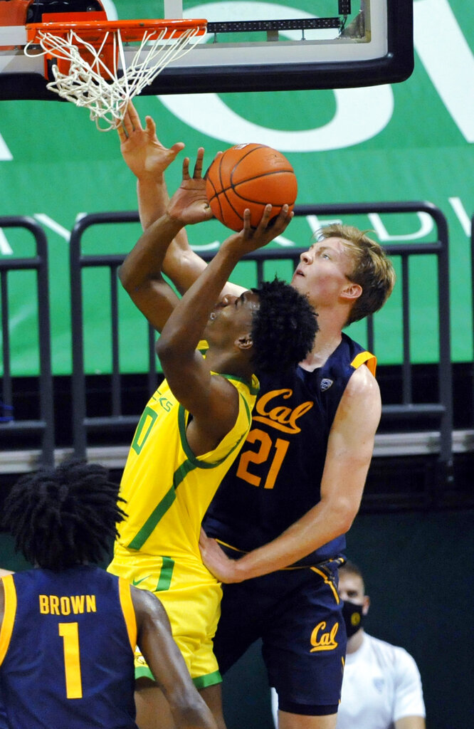 California forward Lars Thiemann (21) contests the shot of Oregon forward Eric Williams Jr. (50) during the first half of an NCAA college basketball game in Eugene, Ore., Friday, Dec. 31, 2020. (AP Photo/Andy Nelson)