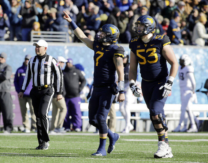 West Virginia quarterback Will Grier (7) and offensive lineman Colton McKivitz (53) celebrate a touchdown during the first half of an NCAA college football game against TCU, Saturday, Nov. 10, 2018, in Morgantown, W.Va. (AP Photo/Raymond Thompson)