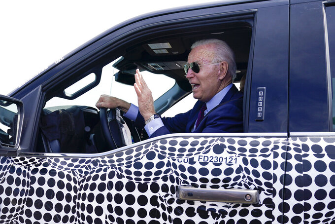 FILE - In this May 18, 2021 file photo, President Joe Biden stops to talk to the media as he drives a Ford F-150 Lightning truck at Ford Dearborn Development Center in Dearborn, Mich.  On Friday, May 21, The Associated Press reported on stories circulating online incorrectly claiming Biden was caught fake driving a Ford F-150 Lightning truck during a visit to a Ford safety testing center Tuesday.  (AP Photo/Evan Vucci, File)