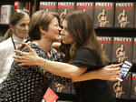 Patrick, right, hugs Julie Grunwald after autographing her new book during a book signing in Charlotte, N.C., Thursday, jan. 4, 2018. (AP Photo/Chuck Burton)