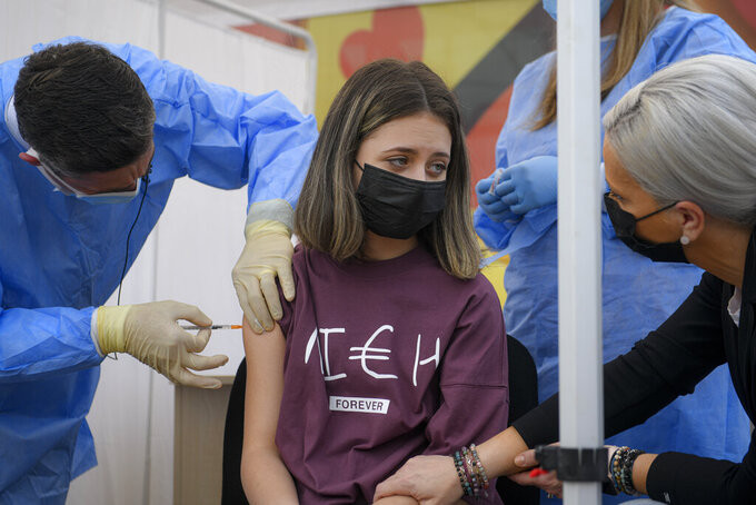 A girl gets a Pfizer BioNTech COVID-19 vaccine in Bucharest, Romania, Wednesday, June 2, 2021. Romania has started the vaccination campaign for children between the ages of 12 and 15. (AP Photo/Andreea Alexandru)