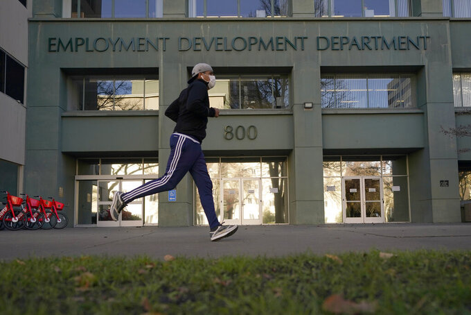 FILE — In his Dec. 18, 2020 file photo a runner passes the office of the California Employment Development Department in Sacramento, Calif. California reported a significant surge in unemployment claims last week for independent contractors, accounting for more than a quarter of all such climbs nationally and raising concerns about a return of widespread fraud, Thursday, Jan. 21, 2021. (AP Photo/Rich Pedroncelli, File)