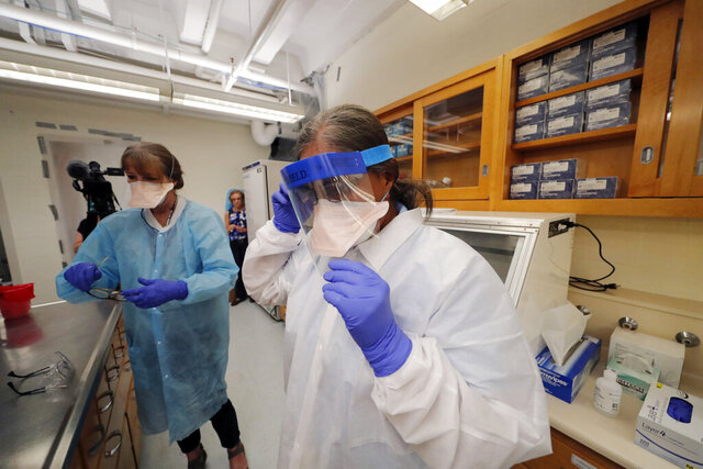 Cindy Morris, left, and Swarnamala Ratnayaka don personal protective equipment before preparing RNA for testing for the new coronavirus at the molecular pathology lab at Tulane University School of Medicine in New Orleans, Thursday, April 2, 2020. The test is identical to the PCR test being used by the Centers for Disease Control to ease the testing crisis and stop the spread of COVID-19, which has hit the New Orleans area especially hard. (AP Photo/Gerald Herbert)