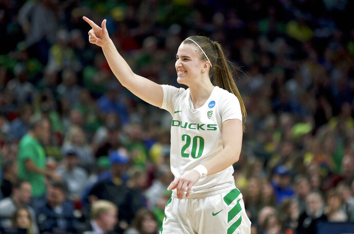 FILE - In this March 29, 2019, file photo, Oregon guard Sabrina Ionescu gestures toward the bench during the second half of the team's regional semifinal against South Dakota State in the NCAA women's college basketball tournament, in Portland, Ore. Oregon is No. 1 for the first time in school history while Tennessee's streak of 42 straight appearances in The Associated Press preseason Top 25 is over. The Ducks, led by sensational guard Sabrina Ionescu, garnered 25 of the 28 first-place votes from the national media panel to earn the top ranking in the poll released Wednesday, Oct. 30, 2019. (AP Photo/Craig Mitchelldyer, File)