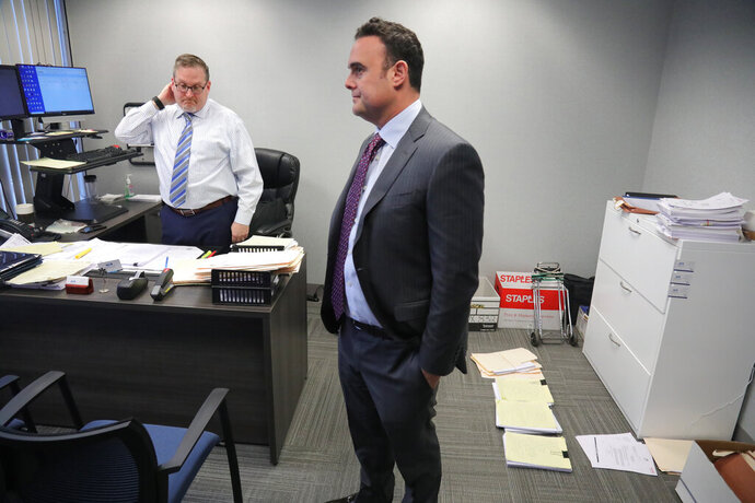 In this Tuesday, Oct. 29, 2019, photo, attorney Adam Slater, right, meets with his firm's managing attorney, Steven Alter, left, in Melville, N.Y. Slater said since New York state opened its one-year window allowing sex abuse suits with no statute of limitations, his firm has signed up nearly 300 new clients, prompting new hires of paralegals to field calls. (AP Photo/Bebeto Matthews)