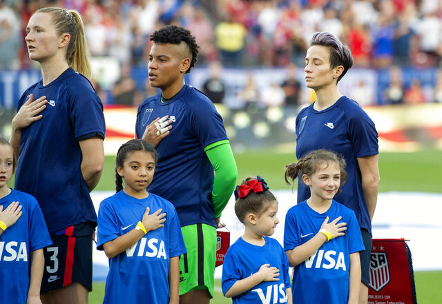 United States midfielder Samantha Mewis (3), goalkeeper Adrianna Franch, center, and forward Megan Rapinoe, right, stand with their jerseys turned inside out during the playing of the national anthem before a SheBelieves Cup women's soccer match against Japan, Wednesday, March 11, 2020 at Toyota Stadium in Frisco, Texas. (AP Photo/Jeffrey McWhorter)