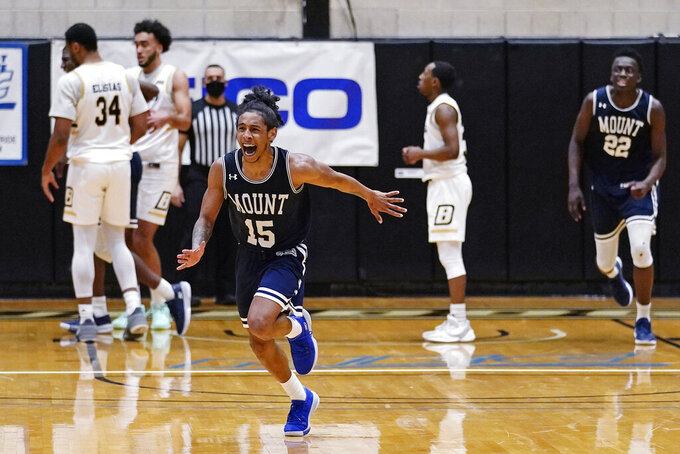Mount St. Mary's guard Damian Chong Qui (15) runs toward his bench while celebrating with teammates after their win in an NCAA college basketball game for the Northeast Conference men's tournament championship against Bryant, Tuesday, March 9, 2021, in Smithfield, R.I. (AP Photo/Charles Krupa)