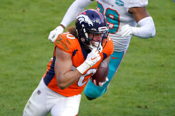 Denver Broncos running back Phillip Lindsay (30) runs as Miami Dolphins free safety Brandon Jones pursues during the first half of an NFL football game, Sunday, Nov. 22, 2020, in Denver. (AP Photo/Jack Dempsey)