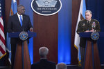 Defense Secretary Lloyd Austin, left, looks towards Joint Chiefs Chairman Gen. Mark Milley as he speaks during a press briefing at the Pentagon, Wednesday, July 21, 2021 in Washington. (AP Photo/Kevin Wolf)