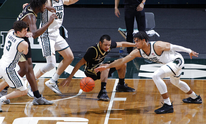 Michigan State's Malik Hall, right, and Foster Loyer (3) and Western Michigan's Rafael Cruz Jr., center, and Titus Wright vie for the ball during the second half of an NCAA college basketball game, Sunday, Dec. 6, 2020, in East Lansing, Mich. (AP Photo/Al Goldis)