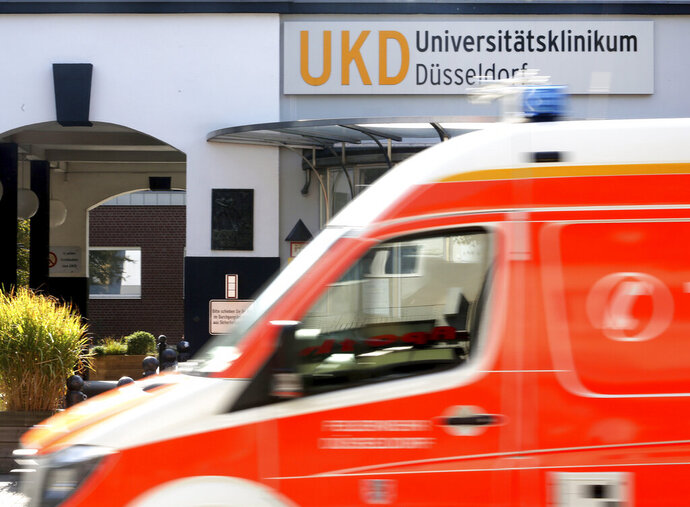 An ambulance drives past the University Hospital in Duesseldorf, Germany, Tuesday, Sept. 15, 2020. German authorities say a hacker attack caused the partial failure of IT systems at a major hospital in Duesseldorf, and a woman who needed urgent admission died after she had to be taken to another city for treatment. (Roland Weihrauch/dpa via AP)