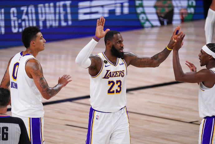 Los Angeles Lakers' LeBron James (23) celebrates with teammates Kyle Kuzma, left, and Rajon Rondo, right, during the second half of an NBA conference semifinal playoff basketball game against the Houston Rockets Tuesday, Sept. 8, 2020, in Lake Buena Vista, Fla. The Lakers won 112-102. (AP Photo/Mark J. Terrill)