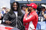 Alvin Kamara, left, running back with the NFL football New Orleans Saints, talks with driver Bubba Wallace before a NASCAR Cup Series auto race at Nashville Superspeedway Sunday, June 20, 2021, in Lebanon, Tenn. (AP Photo/Mark Humphrey)