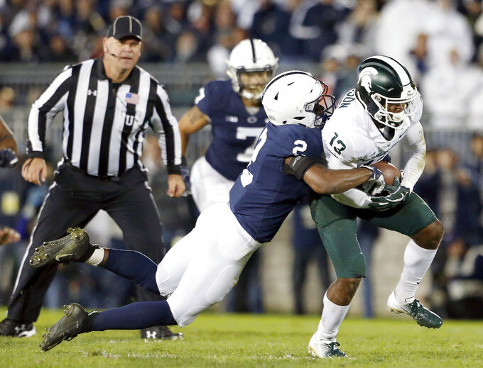 Penn State's Donovan Johnson (2) tackles Michigan State's Laress Nelson (13) after a catch during the second half of an NCAA college football game in State College, Pa., Saturday, Oct. 13, 2018. (AP Photo/Chris Knight)
