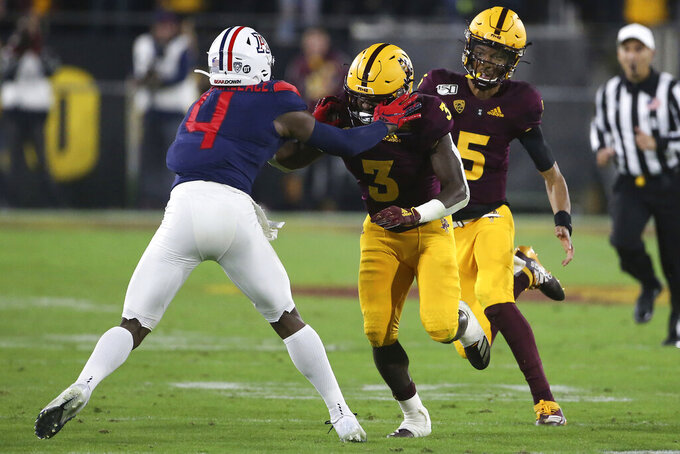 Arizona State quarterback Jayden Daniels (5) gets a block from his running back Eno Benjamin (3) against Arizona's Christian Roland-Wallace during the first half of an NCAA college football game, Saturday, Nov. 30, 2019, in Tempe, Ariz. (AP Photo/Darryl Webb)