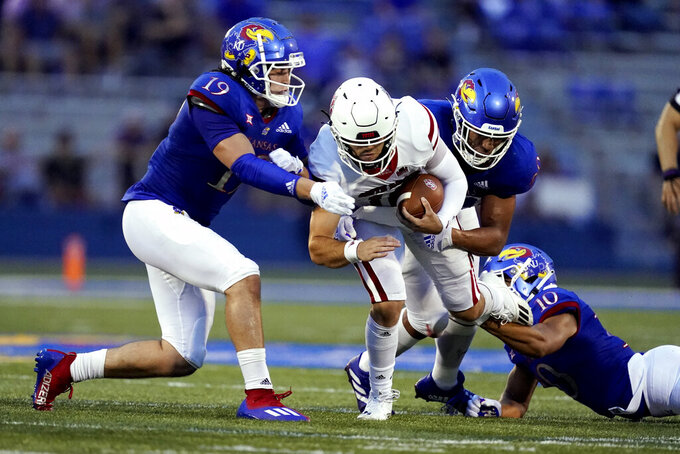 South Dakota quarterback Carson Camp (18) is tacked by Kansas linebacker Gavin Potter (19) and defensive lineman Malcolm Lee, right, during the first half of an NCAA college football game Friday, Sept. 3, 2021, in Lawrence, Kan. (AP Photo/Charlie Riedel)