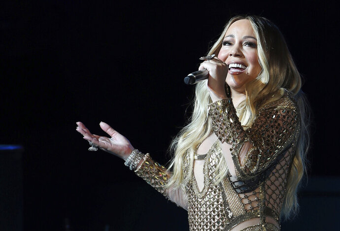FILE - This Oct. 20, 2019 file photo shows Mariah Carey performing during a concert celebrating Dubai Expo 2020 One Year to Go in Dubai, United Arab Emirates. Carey is  among the artists who will be inducted into the Songwriters Hall of Fame on June 11, 2020, in New York City. (AP Photo/Kamran Jebreili, File)
