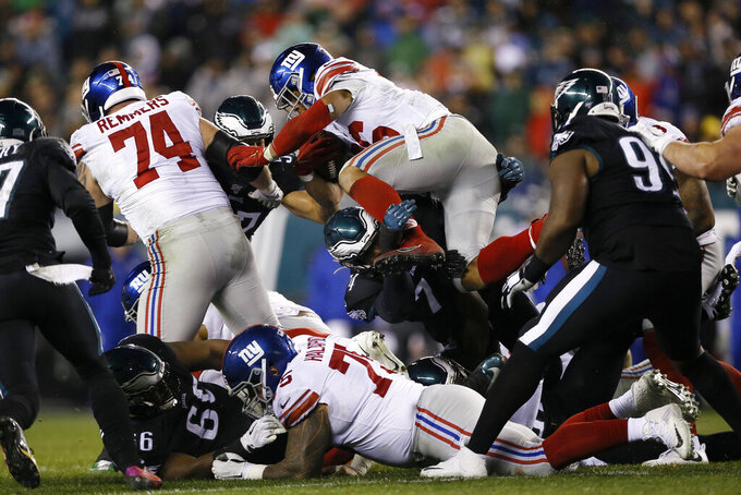 New York Giants' Saquon Barkley (26) leaps over Philadelphia Eagles' Daeshon Hall (74) during the first half of an NFL football game, Monday, Dec. 9, 2019, in Philadelphia. (AP Photo/Michael Perez)