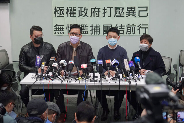 Former Democratic Party legislators Andrew Wan, left, Lam Cheuk-ting, second left, and Helena Wong, right, attend a press conference after being released on bail in Hong Kong, Friday, Jan. 8, 2021. Some former Hong Kong legislators and pro-democracy activists were released on bail late Thursday, after being arrested under Hong Kong's national security law as part of Wednesday's mass arrests of 53 people. The Chinese in the background reads