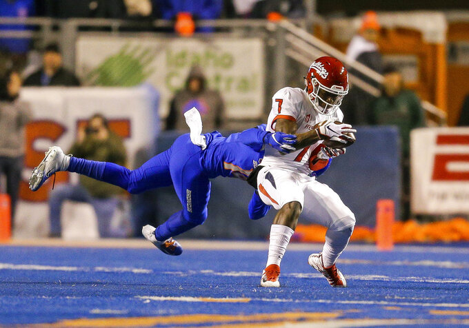 Fresno State wide receiver Derrion Grim (7) hangs on to the ball for a reception as a Boise State defender tries to tackle him in the second half of an NCAA college football game, Friday, Nov. 9, 2018, in Boise, Idaho. Boise State won 24-17 over Fresno State. (AP Photo/Steve Conner)