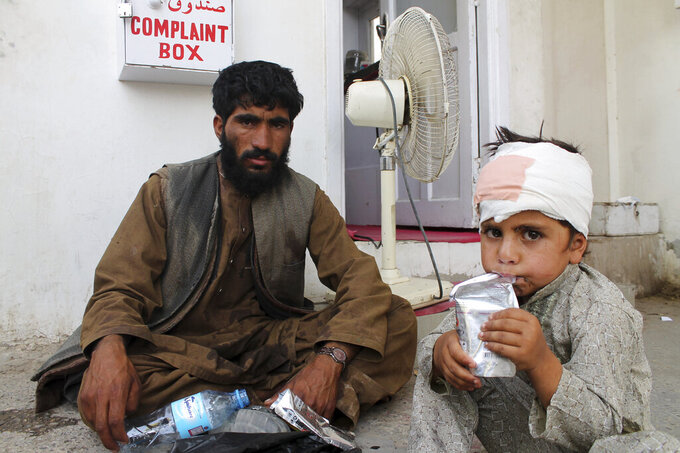 A boy who was injured boy in a deadly attack on a market sits on the ground at a hospital in Helmand province, Monday, June 29, 2020. A car bombing and mortar shells fired at a busy market in southern Afghanistan's Helmand province on Monday killed over 20 people, including children, a statement from a provincial governor's office said. (AP Photo/Abdul Khaliq)
