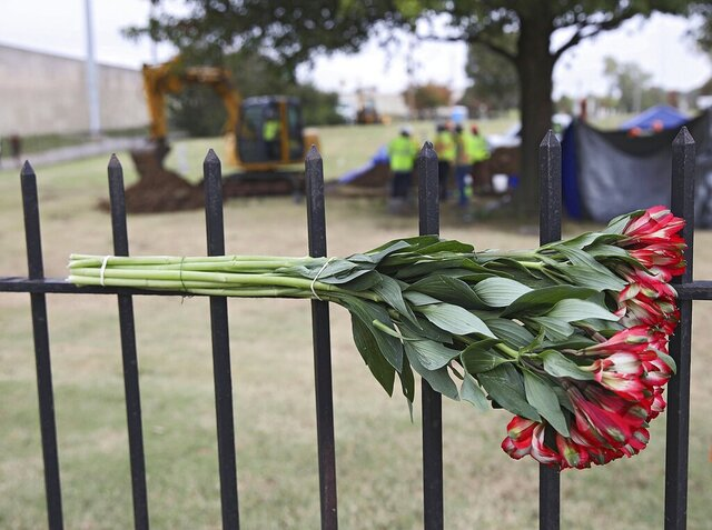 Flowers left by a mourner hang on a fence as crews work on a second test excavation and core sampling in the search for remains at Oaklawn Cemetery from the 1921 Tulsa Race Massacre Wednesday, Oct. 21, 2020. (Mike Simons/Tulsa World via AP)