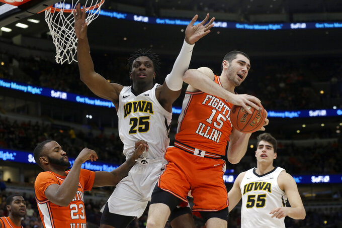 Illinois's Giorgi Bezhanishvili (15) grabs a rebound against Iowa's Tyler Cook (25) during the first half of an NCAA college basketball game in the second round of the Big Ten Conference tournament, Thursday, March 14, 2019, in Chicago. (AP Photo/Kiichiro Sato)