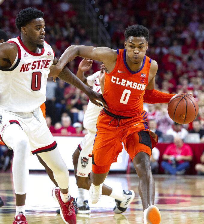 Clemson's Clyde Trapp, right, drives against North Carolina State's DJ Funderburk, left, during an NCAA college basketball game in Raleigh, N.C., Saturday, Jan. 26, 2019. (AP Photo/Ben McKeown)