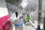 A worker wearing protective gears sprays disinfectant as a precaution against the coronavirus at a shopping street in Seoul, South Korea, Thursday, Feb. 27, 2020. The new illness persists in the worst-hit areas and spreads beyond borders. (AP Photo/Ahn Young-joon)