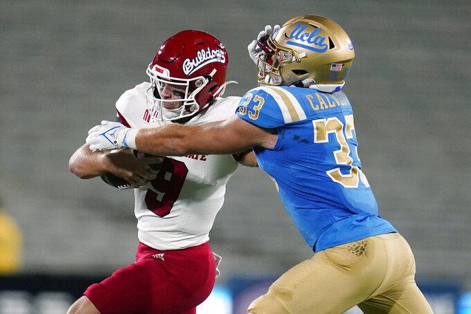 Fresno State quarterback Jake Haener, left, stiff-arms UCLA linebacker Bo Calvert (33) during the first half of an NCAA college football game Saturday, Sept. 18, 2021, in Pasadena, Calif. (AP Photo/Marcio Jose Sanchez)