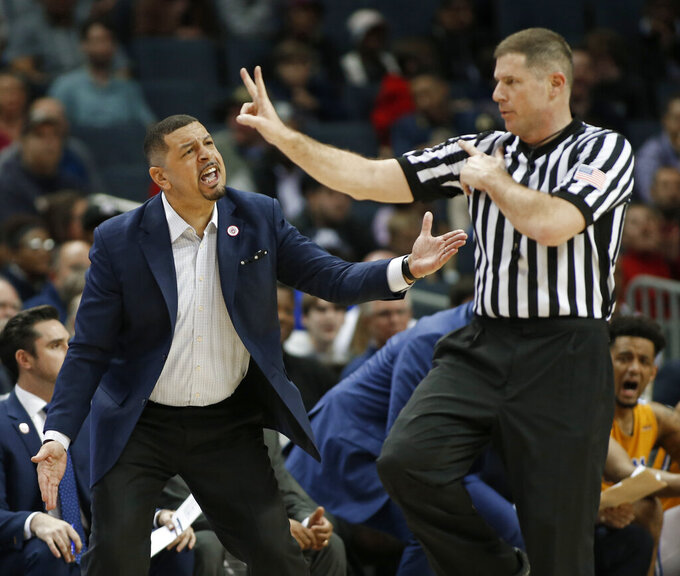 Pittsburgh coach Jeff Capel, left, argues a call during the first half of the team's NCAA college basketball game against Boston College in the Atlantic Coast Conference men's tournament in Charlotte, N.C., Tuesday, March 12, 2019. (AP Photo/Nell Redmond)