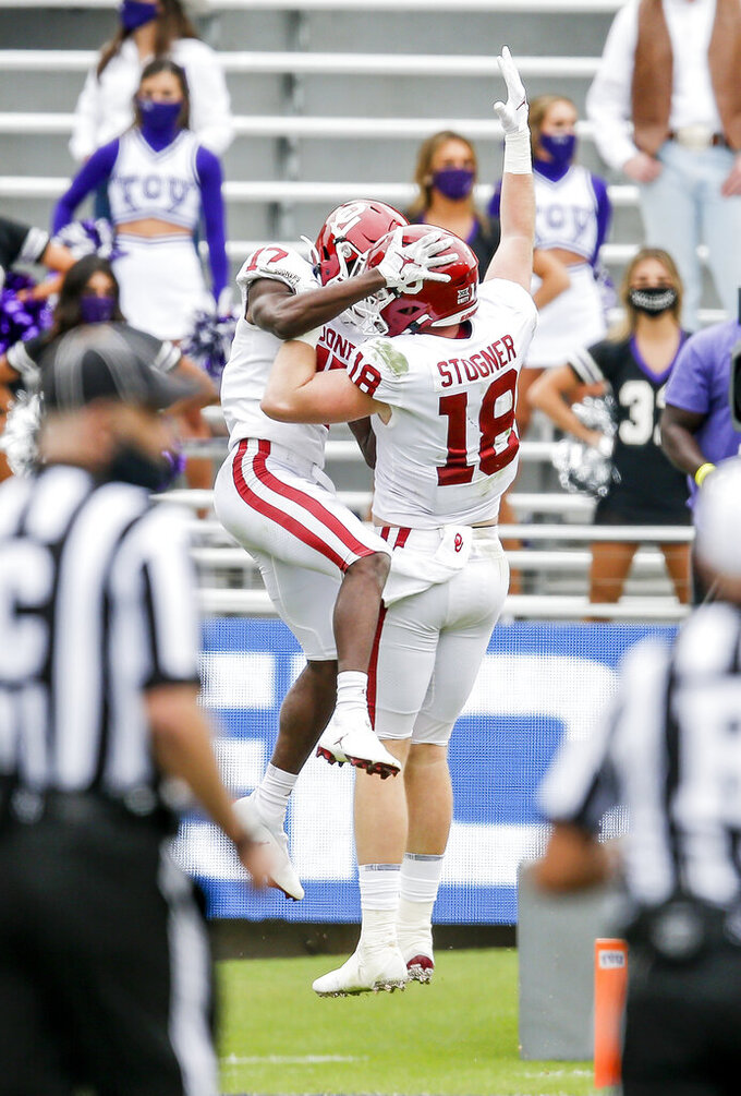 Oklahoma wide receiver Marvin Mims (17) is congratulated by tight end Austin Stogner (18) after scoring a touchdown during the second half of an NCAA college football game against TCU, Saturday, Oct. 24, 2020, in Fort Worth, Texas. (AP Photo/Brandon Wade)